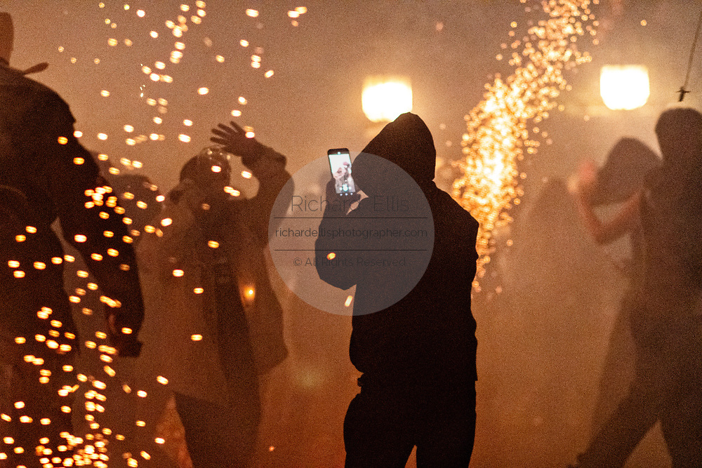 A man wearing a hoodie takes a camera phone picture as sky rockets explode all around during the Alborada festival September 29, 2018 in San Miguel de Allende, Mexico. The unusual festival celebrates the cities patron saint with a two hour-long firework battle at 4am representing the struggle between Saint Michael and Lucifer.