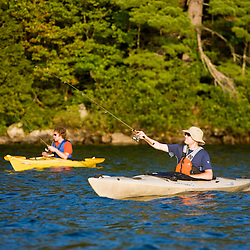 Two men fish from their kayaks on Lake Sunapee at Mount Sunapee State Park in Newbury, New Hampshire.