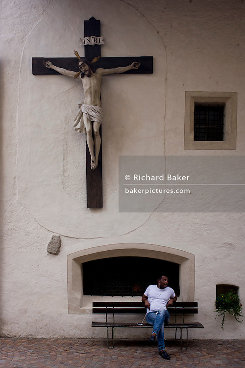 A man sits beneath a large Jesus crucifix on the wall of a church in the town of Klausen-Chiusa in the south Tyrol, Italy.