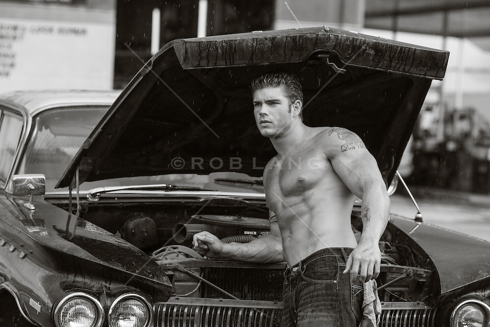 shirtless muscular auto mechanic with dirt on his face and  body at an auto body repair shop