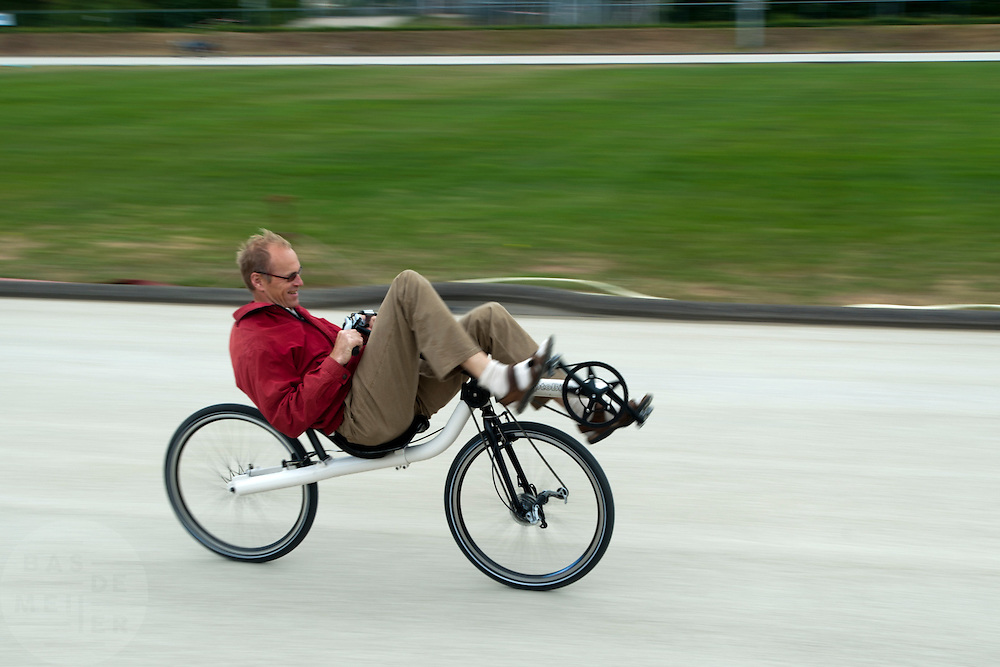 Een ligfietser rijdt over de weg.<br /> <br /> A man is riding a recumbent bike.