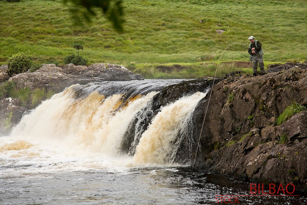 waterfall and fisherman in Erriff river.<br /> County Mayo.  Republic of Ireland.