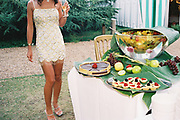 Woman wearing spangled mini dress, holding champagne and admiring the spread of fruit and desserts, in the garden, Posh at Addington Palace, UK, August, 2004