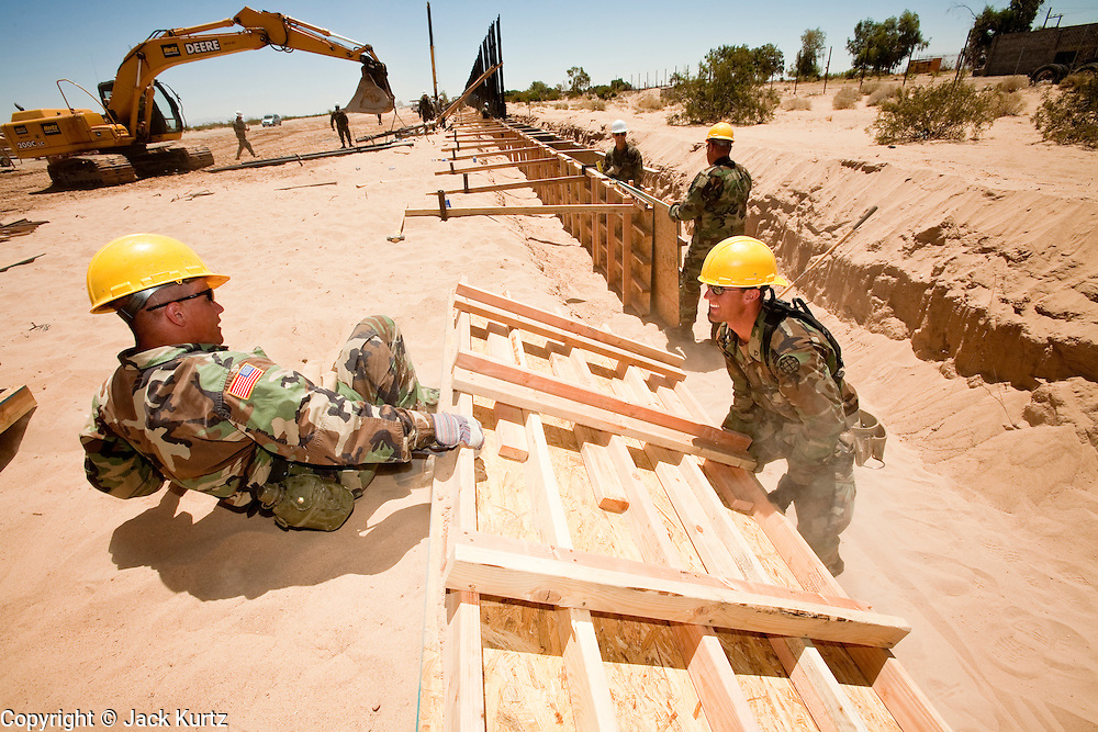 12 JUNE 2006 - SAN LUIS, AZ: Pfc Thomas Carter, left, and Pfc. Josh Richard, lift a concrete form out of a trench on a fence line on the US/Mexico border. Fifty five members of the 116th Engineer Company, Combat Support Engineers, of the Utah Army National Guard are in San Luis, AZ, to build a fence and improve roads east of the San Luis Port of Entry on the US/Mexico border. The unit is the first of an estimated 6,000 US military personnel, almost all of them Army National Guard, who will be dispatched to the US/Mexico border by President Bush to help control immigration on the border. The Guardsmen will primarily build roads and fence and staff surveillance centers. They will not be engaged in first line law enforcement work.  Photo by Jack Kurtz