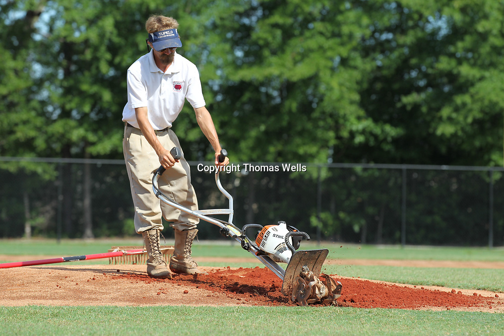Justin Smedley uses a small tiller to mix in new soil and break up the compacted soil before beginning to rebuild and repack the pitching mounds at Ballard Park.