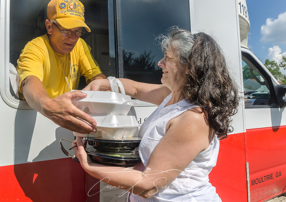 Southern Baptist Disaster Relief team member Jerry Ritter, a member of Blackgum First Baptist Church in Vian, Okla., hands two hot meals to flood survivor Pat Thomas, a member of Healing Place Church of Baton Rouge, Aug. 23, 2016, in Baton Rouge, La. SBDR began preparing an average of 14,000 meals per day after heavy rain caused devastating flooding in Louisiana, Aug. 12-15, 2016. (Photo by Carmen K. Sisson)