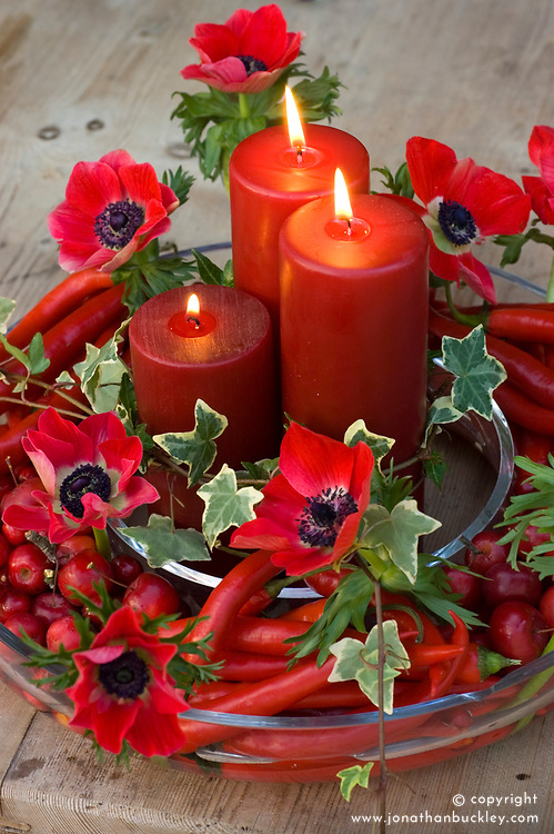 Red candles with Anemone coronaria and chillies