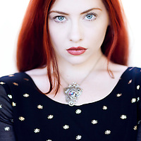 Attractive young woman with long red hair and blue eyes wearing a silver necklace looking at camera