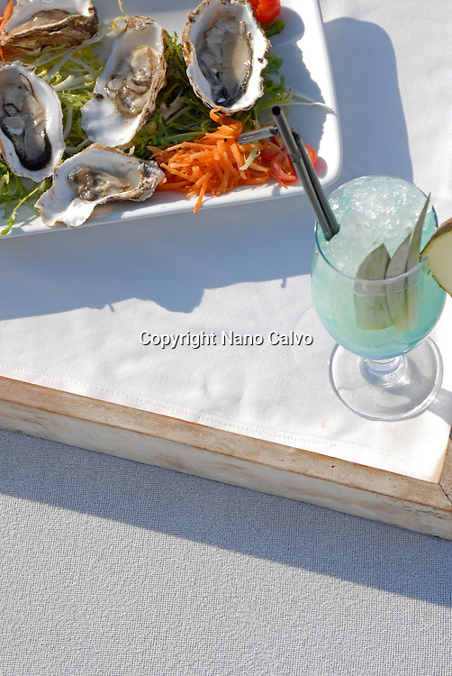 Tray with oysters and a fruit juice on a bed in Blue Marlin beach restaurant, Ibiza, Spain