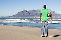 Rear view of man standing with football Table Mountain beach
