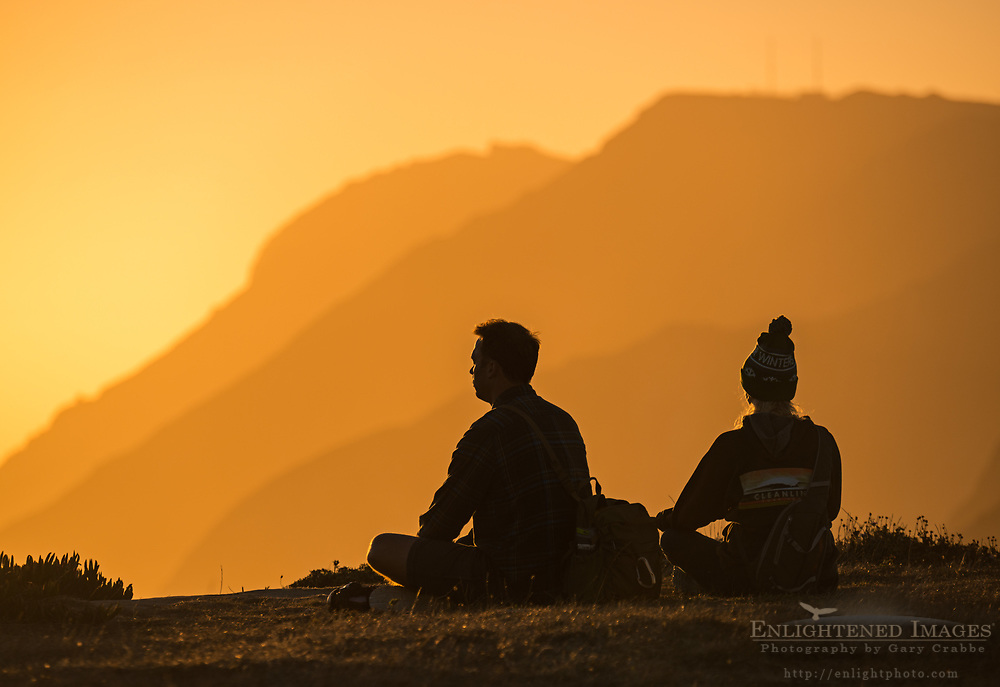 Couple meditating at sunset at the headlands of Point Reyes National Seashore, Marin County, California