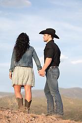 cowboy and a girl looking towards a mountain range