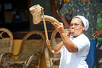 Cook from Arraras Lodge blowing on cow horn,  The Pantanal, Mato Grosso, Brazil