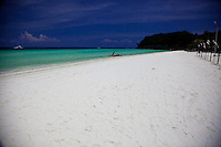Beautiful white sandy beach with clear tropical turquoise waters gently lapping at its edge under the deep blue skies of midday on Boracay, Philippines.