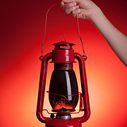 A woman holds up a sooty kerosene lantern. Red backdrop with orange spotlight gives the impression of light eminating from the lantern.