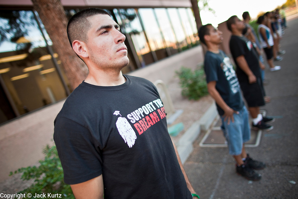 "Sept. 19 - PHOENIX, AZ: JOSE PATINO, from Phoenix, stands in formation behind US Senator John McCain's office in Phoenix. About 30 people met in front of US Sen. John McCain's office in Phoenix Sunday night to demonstrate in support of the DREAM Act, which is scheduled to be debated in the US Senate on Tuesday, Sept 21. The Development, Relief and Education for Alien Minors Act (The ""DREAM Act"") is a piece of proposed federal legislation in the United States that was introduced in the United States Senate, and the United States House of Representatives on March 26, 2009. This bill would provide certain illegal immigrant students who graduate from US high schools, who are of good moral character, arrived in the U.S. as minors, and have been in the country continuously for at least five years prior to the bill's enactment, the opportunity to earn conditional permanent residency. In the early part of this decade McCain supported legislation similar to the DREAM Act, but his position on immigration has hardened in the last two years and he no longer supports it. The protesters, mostly area students, marched and drilled to show their support for the US military and then held a candle light vigil.  Photo by Jack Kurtz"