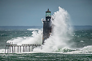 An absolutely massive waves crashes over Ram Island Ledge Lighthouse just off of Fort Williams and Portland Head Light in Casco Bay.