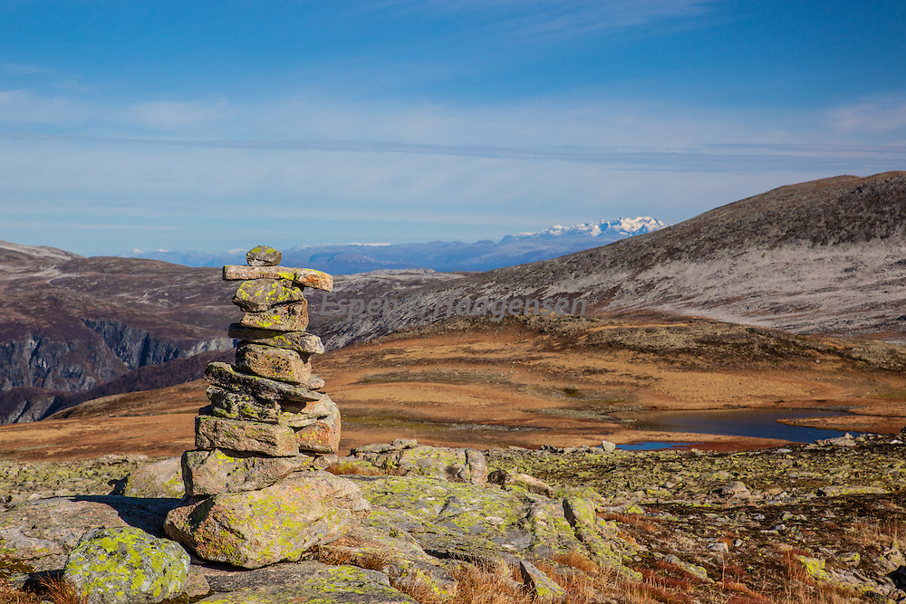 A cairn and Hurrungane (Jotunheimen) covered in white