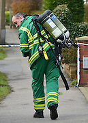 © Licensed to London News Pictures. 13/04/2013. Ruislip, UK an ambulance man with breathing apparatus. Police and ambulance crews at the scene where a woman and two children have been found dead at a house in Ruislip, West London. Police were called by London Ambulance Service at approx 1840 hrs on Friday 12 April to reports of a woman and two children found deceased at an address in Midcroft Road. Photo credit : Stephen Simpson/LNP