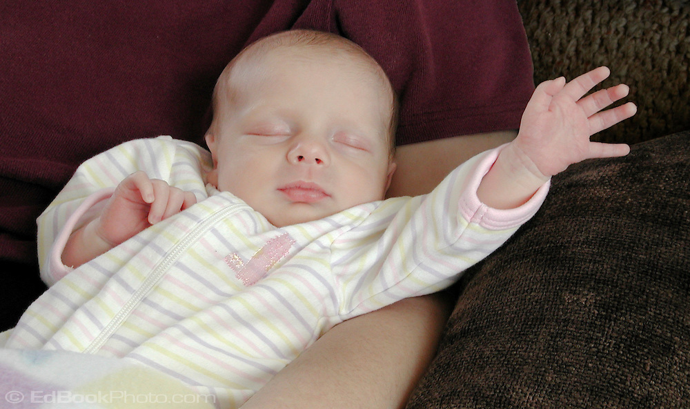 A two-week-old infant reaches with her hand while asleep as if waving to the world.