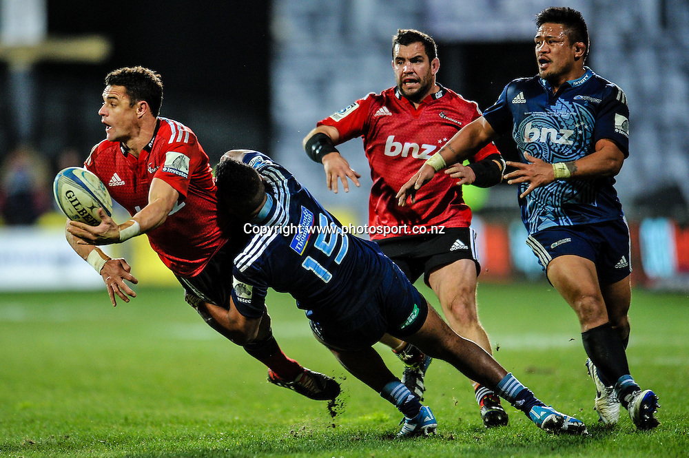 Dan Carter of the Crusaders  off loads the ball in the tackle off Lolagi Visinia of the Blues in the Super rugby match,  Crusaders v The Blues, at AMI Stadium, Christchurch, on the 5 July 2014 . Photo:John Davidson/www.photosport.co.nz