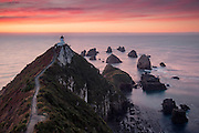 A serene sunrise awakens the wildlife nestled along the rocky headlands of Nugget Point, Catlins, New Zealand.
