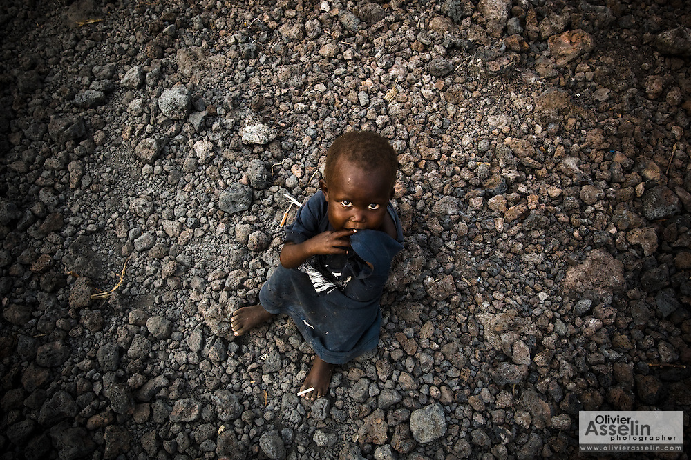 A boy sits on volcanic rocks in the middle of a footpath in the Majengo neighborhood in Goma, Eastern Democratic Republic of Congo on Tuesday December 16, 2008.