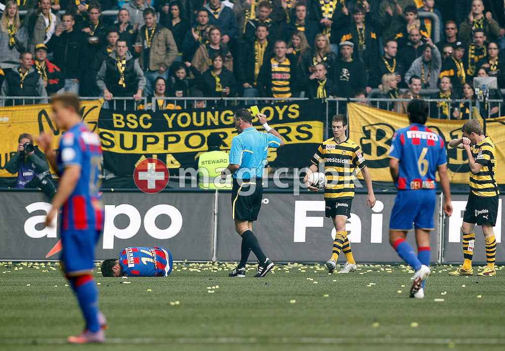 FC Basel midfielder Valentin Stocker is on the ground after being fouled by BSC Young Boys player Christian Schneuwly (R) who has received a yellow card by referee Jerome Laperriere (C) during the Super League (National League A) soccer match between BSC Young Boys (YB) and FC Basel (FCB) at the Stade de Suisse stadium in Bern, Switzerland, Sunday, Mai 16, 2010. BSC Young Boys player Francois Affolter (3rd R) brings the ball back. FC Basel have won the Swiss football championship beating Young Boys of Bern 2-0 in the last match of the season. (Photo by Patrick B. Kraemer / MAGICPBK)