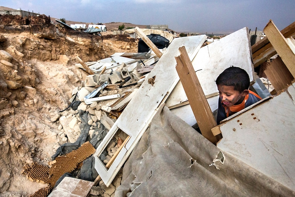 A boy explores the ruins of his newly demolished home in the Bedouin camp of Al Auja. Dec. 4, 2013. West Bank, Palestinian Territories. (Photo by Gabriel Romero/Alexia Foundation ©2014)