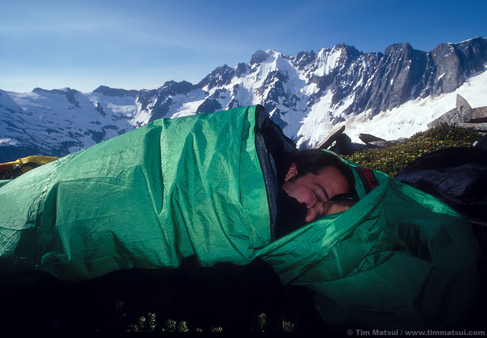 Forrest Murphy sleeps in on a rest day in the North Pickets, North Cascades National Park.