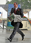 © licensed to London News Pictures. ASCOT, UK.  16/06/11. A man is caught out by a sharp shower. People arrive at Royal Ascot during a torrential downpour of rain.  Ladies Day at Royal Ascot 16 June 2011. Royal Ascot has established itself as a national institution and the centrepiece of the British social calendar as well as being a stage for the best racehorses in the world. Mandatory Credit Stephen Simpson/LNP