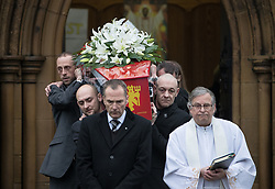 © Licensed to London News Pictures . 20/12/2017. Manchester, UK. The coffin is carried from the church after the service . The funeral of 14-year-old Sam Berkley at Christ Church in Denton , East Manchester . Mourners wear red and white , the colours of Hattersley FC , for whom Berkley played . Amongst their number are pupils and friends from Audenshaw School . Berkley died after being hit by a grey BMW near junction 3 of the M67 in Hyde , East Manchester , on 1st December 2017 . Photo credit: Joel Goodman/LNP