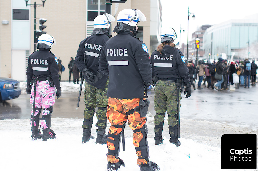 Montreal police, in camouflage pants to protest Quebec pension reforms, stand across the street from the protest. March 15, 2015.