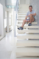 Smiling mid-adult man sitting on staircase holding bottle of water