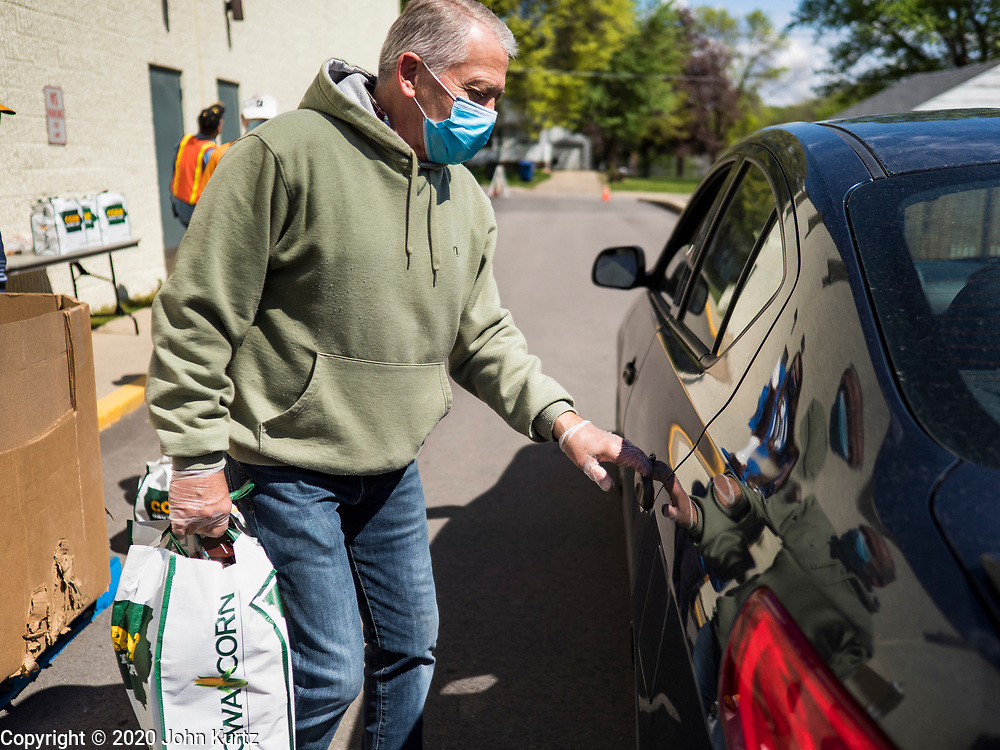 """11 MAY 2020 - DES MOINES, IOWA: RICHARD JESS puts an emergency food package into a client's car at a """"no touch"""" emergency food pantry at DSM First Church in Des Moines. The emergency pantry at DSM First Church expanded from distribution one day a week to three days per week after the COVID-19 pandemic forced the closure of many Iowa businesses. Food banks and emergency pantries in Iowa continue to see increased demand for services, even though the governor is reopening the state's economy. Iowa's unemployment rate for April hasn't been released yet, but based on national trends, it is expected to soar to well over 10% from 3.8& in March. COVID-19 infections continue to skyrocket. On Monday, 11 May, the governor announced that 12,373 people tested positive for coronavirus (SAR-CoV-2) and  271 had died.            PHOTO BY JACK KURTZ"""