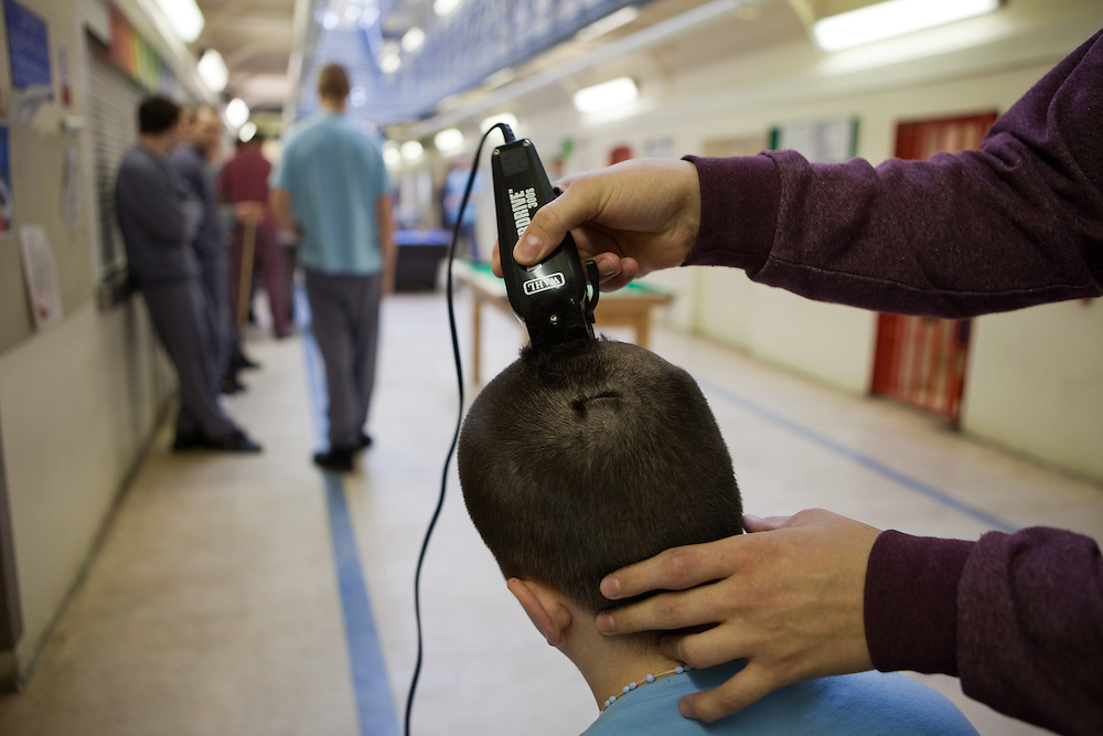 A prisoner having his hair cut by a fellor inmate during their recreation period at YOI Aylesbury.