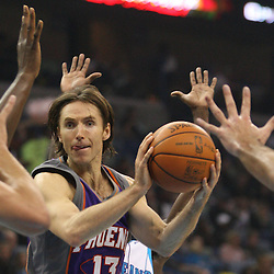 Feb 01, 2010; New Orleans, LA, USA; Phoenix Suns guard Steve Nash (13) passes the ball between the hands of several New Orleans Hornets defenders during the first half at the New Orleans Arena. Mandatory Credit: Derick E. Hingle