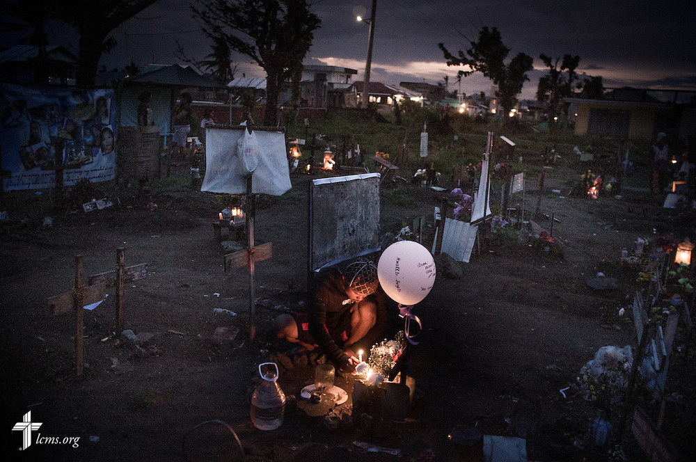 A man lights a candle next to a memorial in a graveyard for  victims of Typhoon Haiyan in Tacloban, Leyte Province, Philippines, on Friday, March 14, 2014. LCMS Communications/Erik M. Lunsford