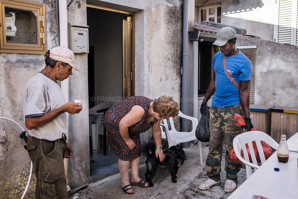 Biagio and Daniel chatting with a local woman during their door to door waste and recycling pickup.  RIACE (ITALY) 01/08/16
