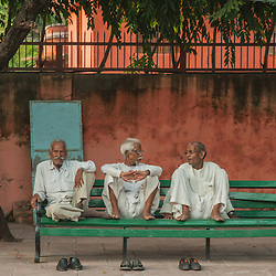 Three old men sitting on a bench talking, in front of a red wall in the city of Agra, India.