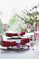 Christmas crackers with name tags on dining table