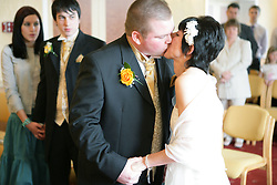 Bride and groom kiss each other after taking marriage vows at a registry office wedding,