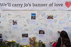 © Licensed to London News Pictures. 17/06/2016. London, UK. Wellwishers, mourners and members of the public sign a wall of remembrance at an evening vigil in Parliament Square for Jo Cox, Labour MP for Batley and Spen, who was murdered the previous day whilst en route to her constituency surgery. Photo credit : Stephen Chung/LNP