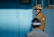 A North Korean soldier (top) looks on as a South Korean soldier stands guard at the truce village of the Panmunjom in the demilitarised zone separating the two Koreas, in Paju, north of Seoul. Photo by Lee Jae-Won (SOUTH KOREA) www.leejaewonpix.com/