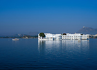 "UDAIPUR, INDIA - CIRCA NOVEMBER 2018:  Lake Palace Hotel formerly known as Jag Niwas in Lake Pichola in Udaipur. The city is the historic capital of the kingdom of Mewar. Surrounded by Aravali Range, which separates it from Thar Desert, and full of lakes Udapiur is also known as the ""City of Lakes"" and dubbed as the most romantic spot of the Indian Continent."