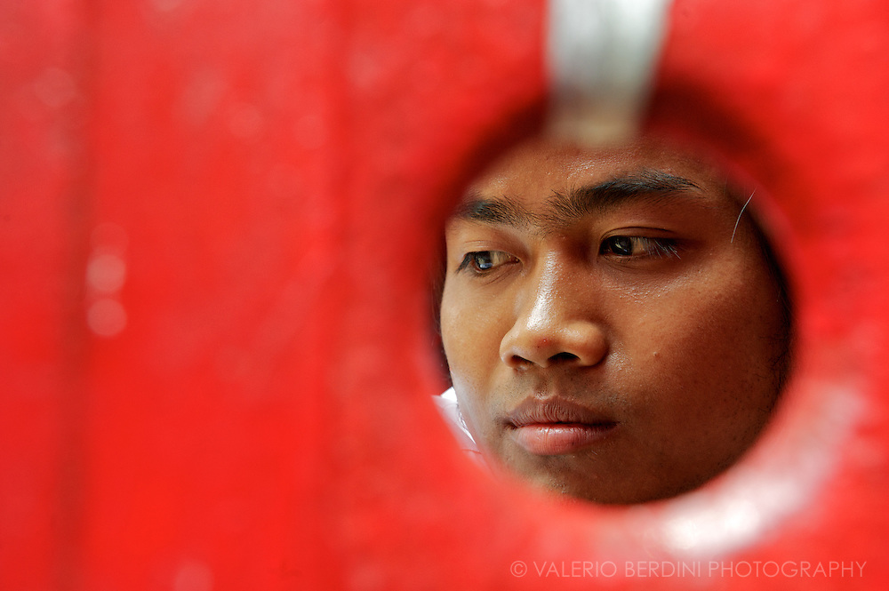 A boy of the NLD security takes a break after the red gate is closed and crowd kept outside of the meeting. Yangon, Myanmar. 2012