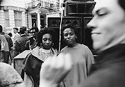 Two girls pose for the camera in front of a sound system as a man passing by dancing to the music inadvertently obstructs its view, Notting Hill Carnival, London, 1989