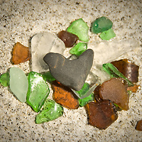 A heart shaped rock on a bed of beach glass