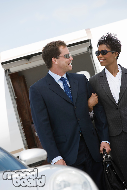 Mid-adult businesswoman and businessman in front of airplane.