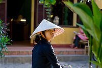 A young woman wearing a traditional conical hat in the streets of Hoi An's old town.